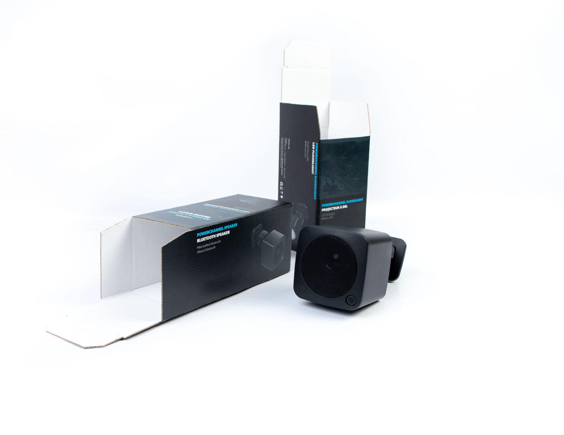 bluetooth speaker next to its cardboard packaging